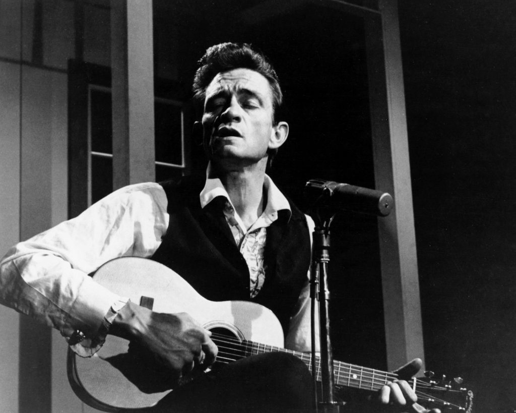 Johnny Cash playing songs on a guitar