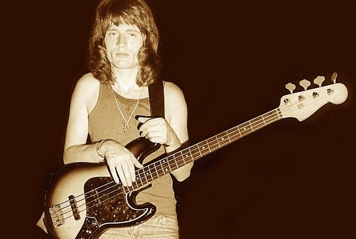 John Paul Jones stands staring at the camera with his bass guitar strapped on