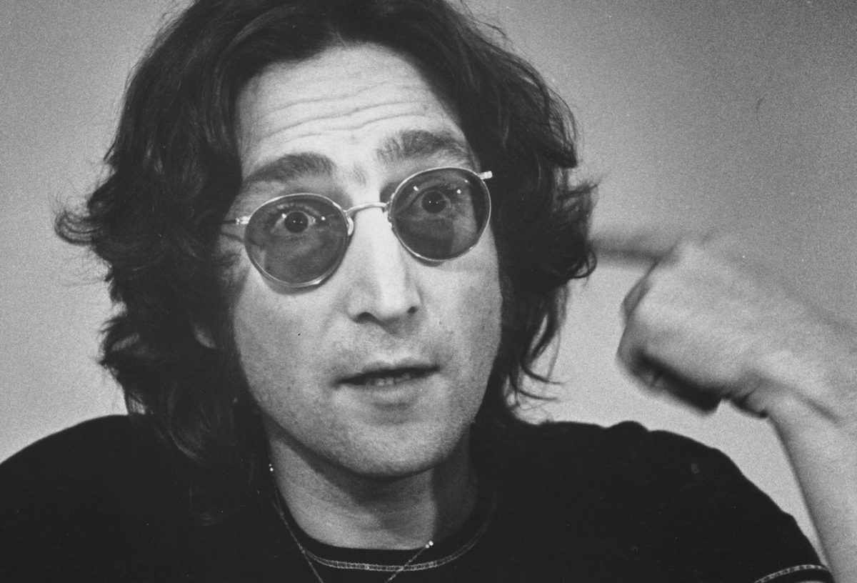 John Lennon, wearing sunglasses, points to his head during a '74 interview.