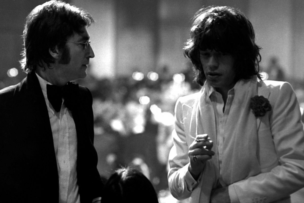 John Lennon looks at Mick Jagger, who's smoking a cigarette and looking away