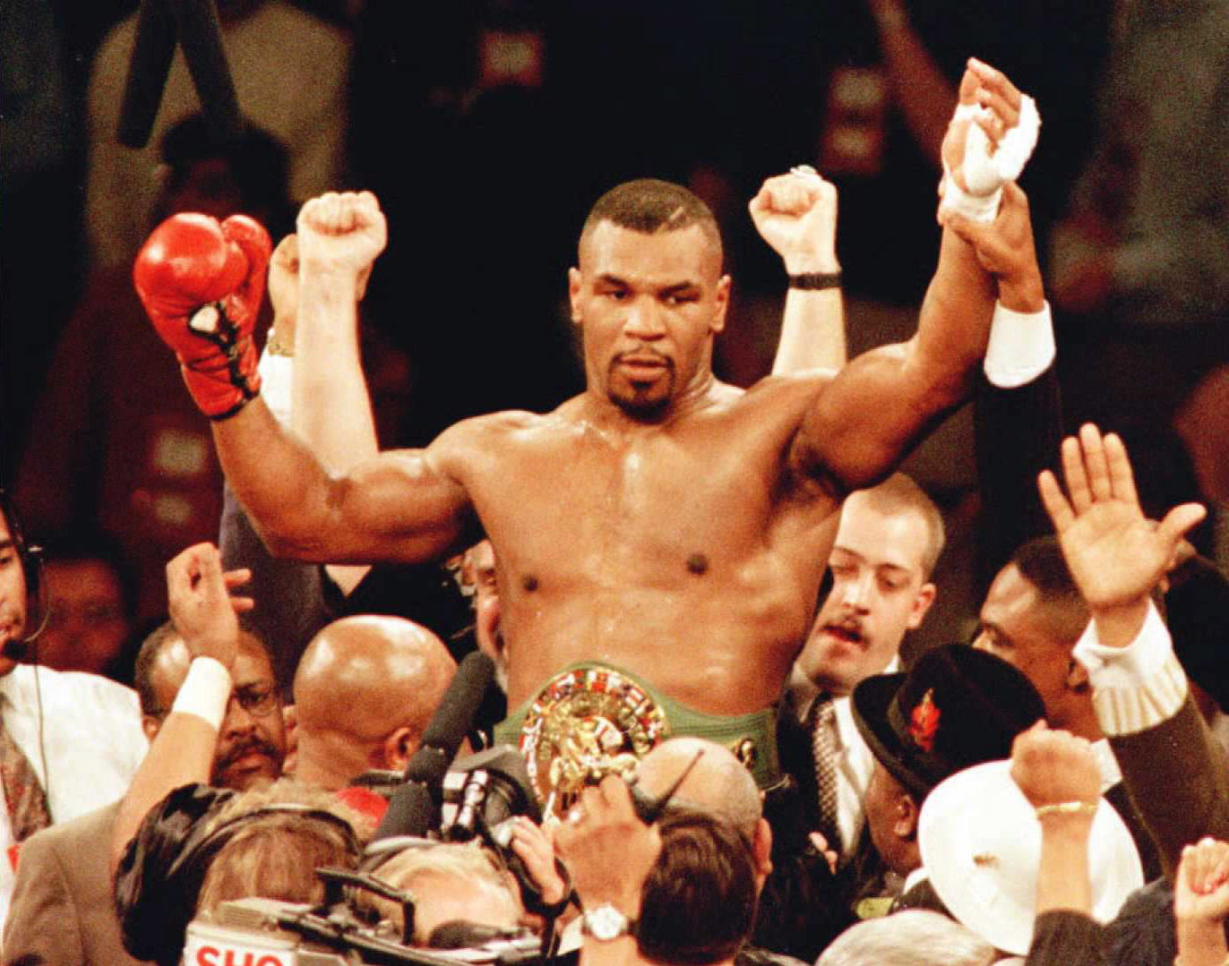 Mike Tyson is lifted into the air wearing the championship belt after defeating WBC heavyweight champion Frank Bruno