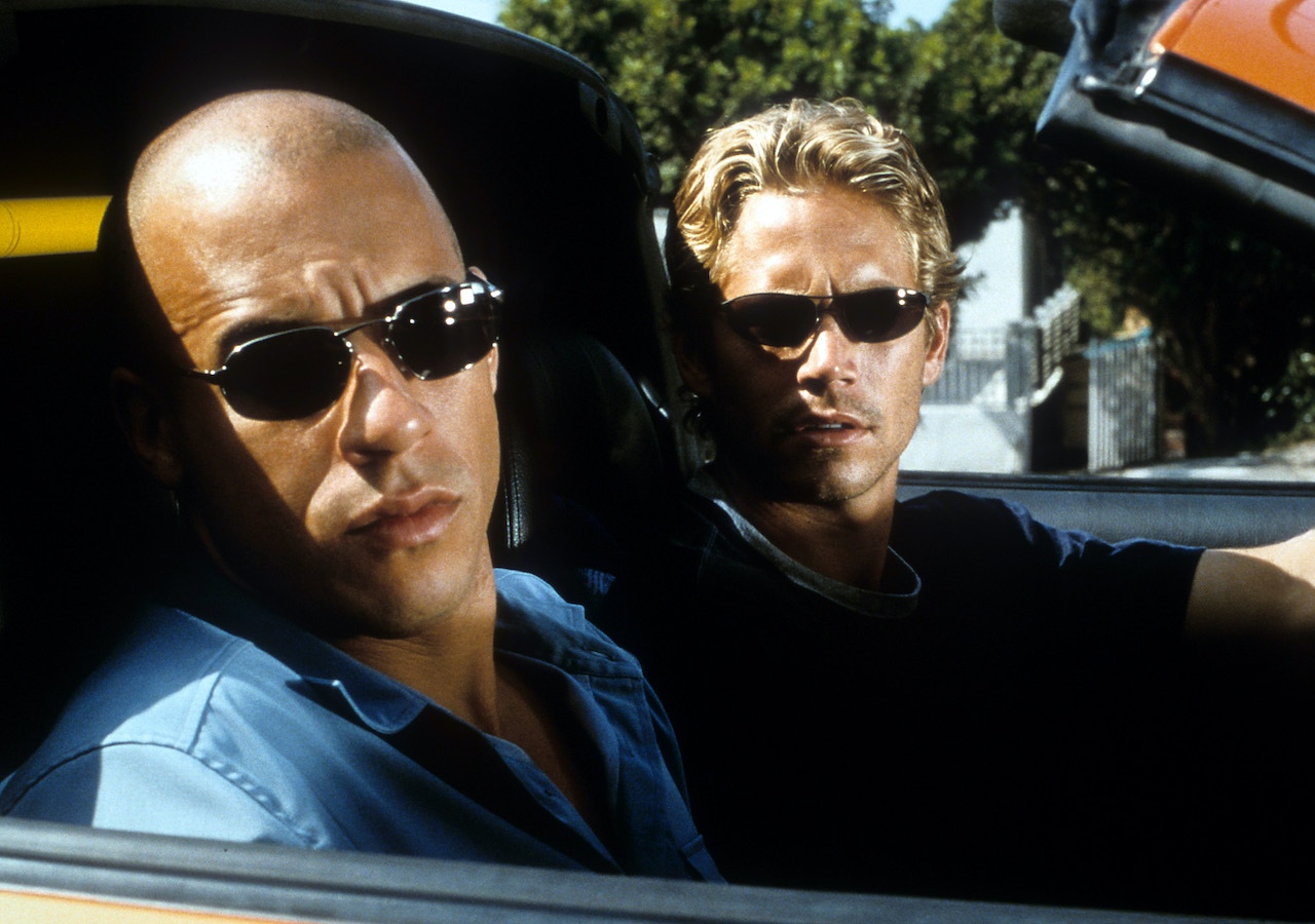 Vin Diesel and Paul Walker looking from car in a scene from the film 'The Fast And The Furious'