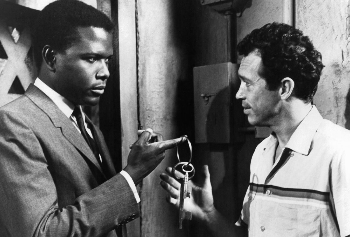 Sidney Poitier hands Warren Oates a jail cell key during the 'In the Heat of the Night' shoot.