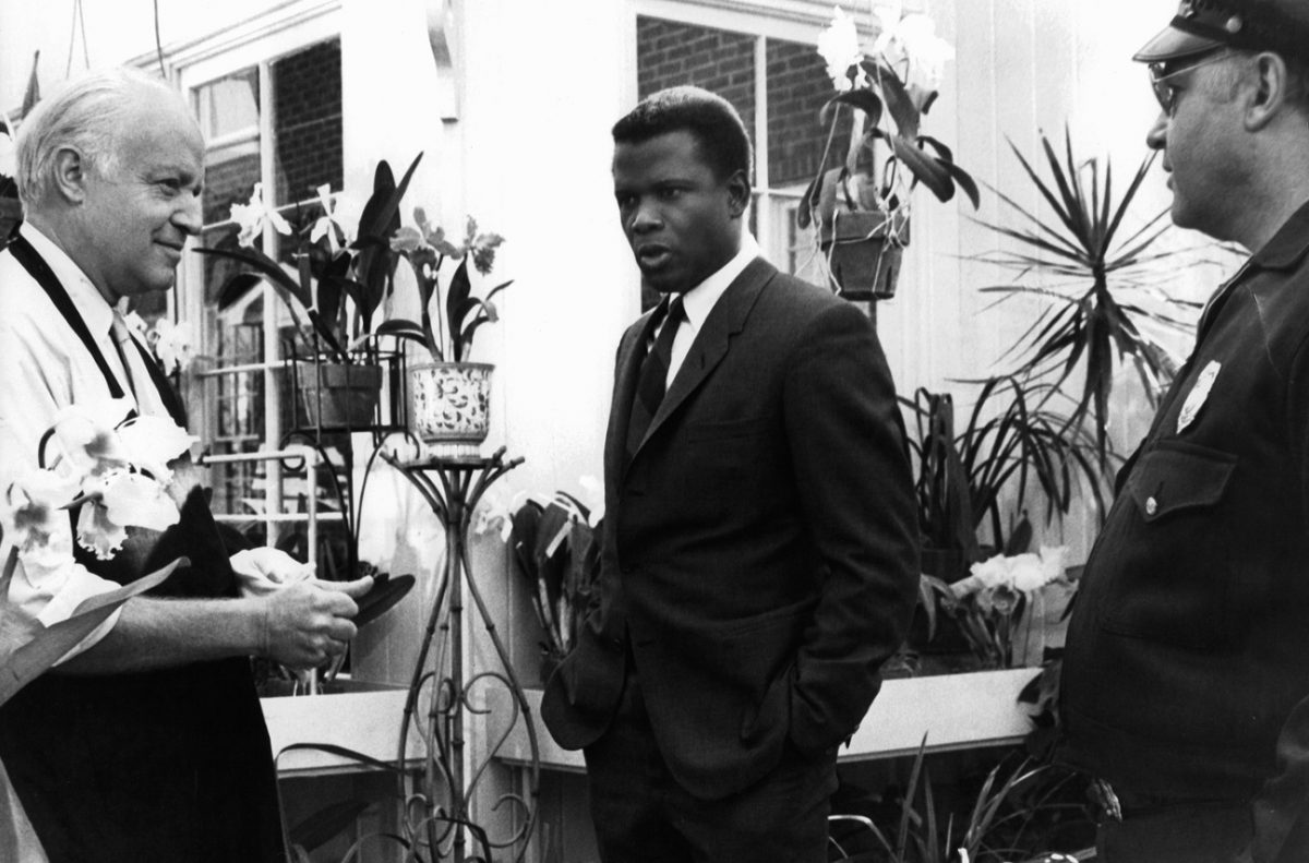 Sidney Poitier stands between two actors in a greenhouse in 'In the Heat of the Night.'
