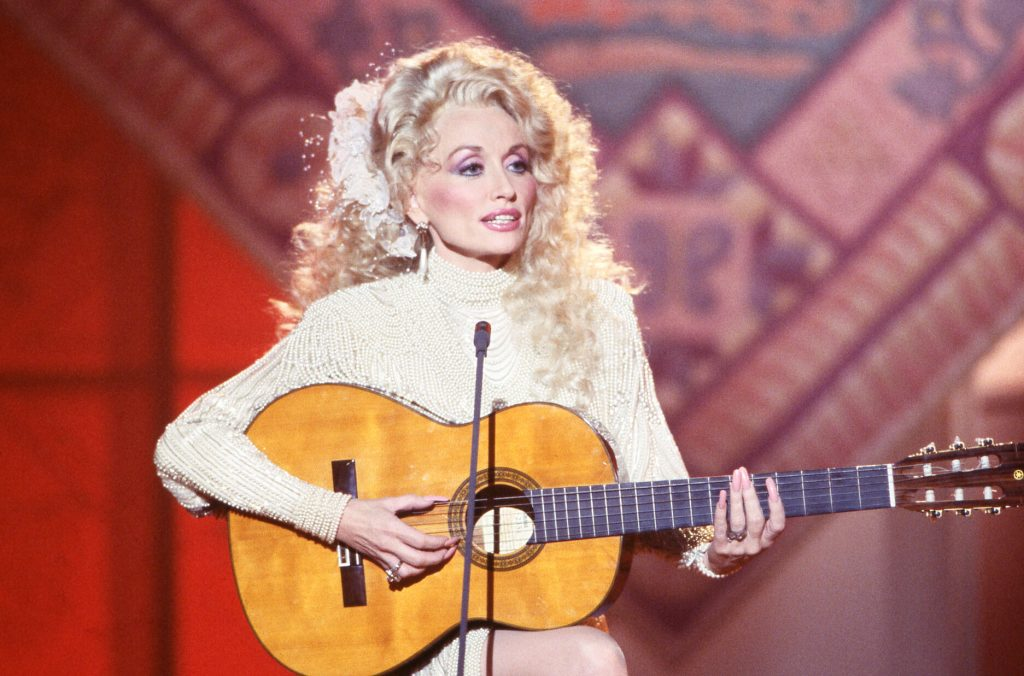 Dolly Parton sitting playing guitar in a white dress.