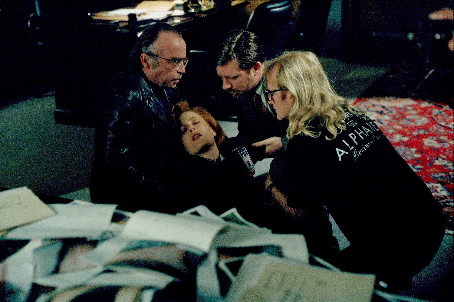 Agent Scully (Gillian Anderson, C) is saved from a fall by The Lone Gunmen (L-R: Tom Braidwood as Frohike, Bruce Harwood as Byers, and Dean Haglund as Langley) in The X-Files