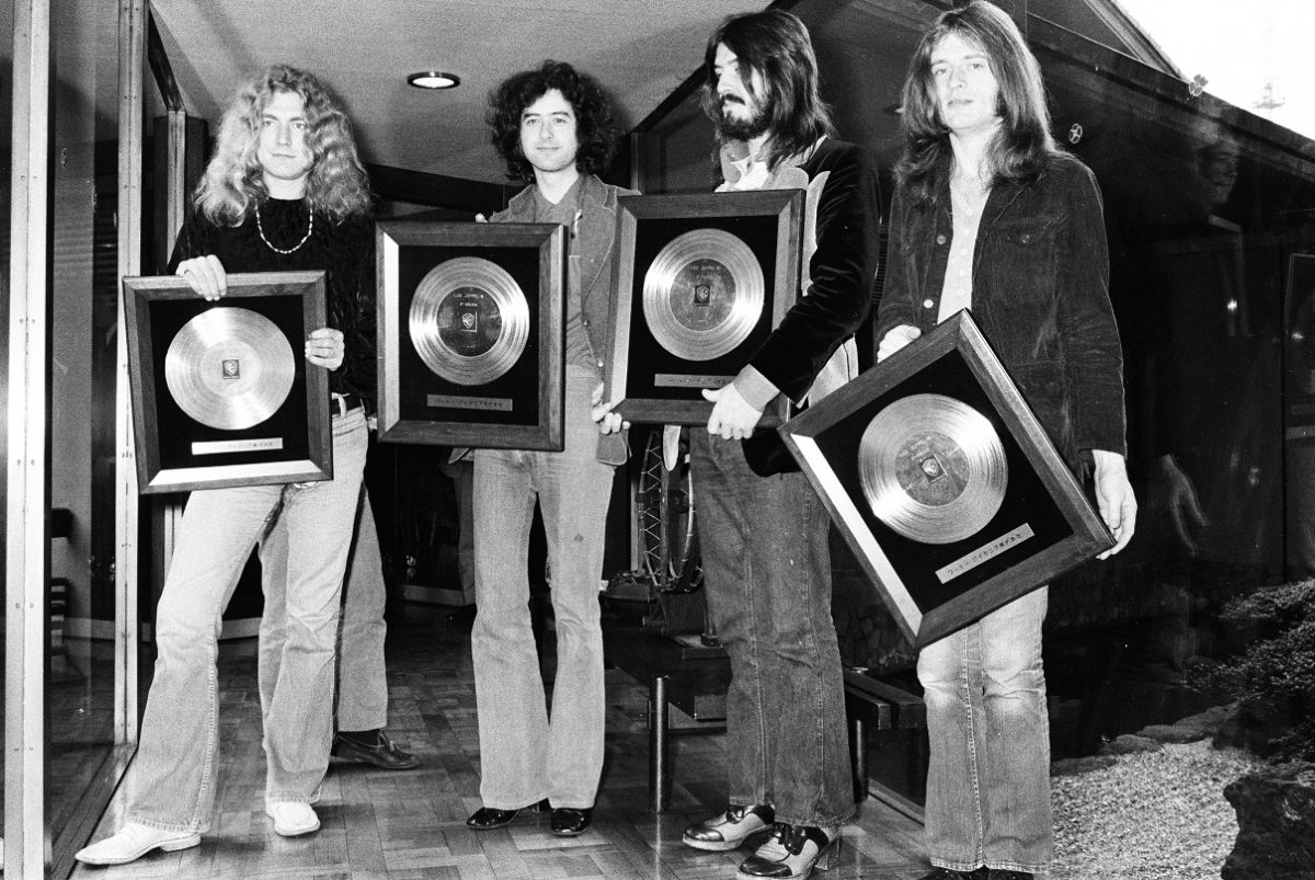 The four members of Led Zeppelin hold framed gold records and smile for the camera in 1972.
