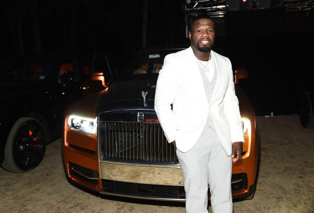 """Curtis """"50 Cent"""" Jackson dressed in white standing in front of a Rolls Royce"""