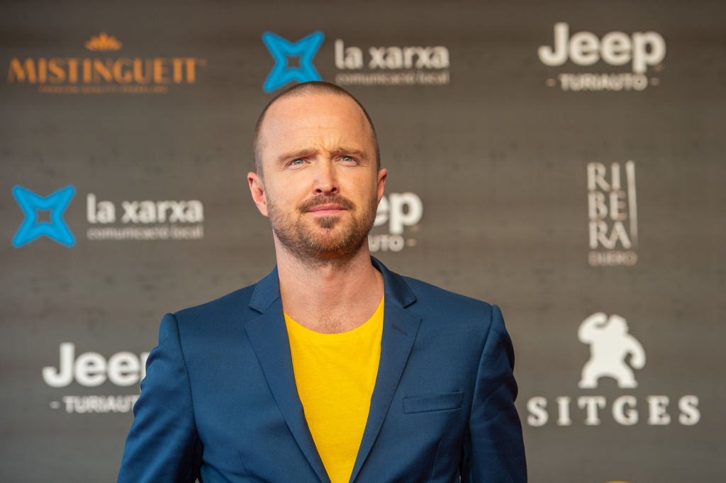 Aaron Paul attends 'El Camino: A Breaking Bad Movie' in a blue suit jacket and yellow undershirt.