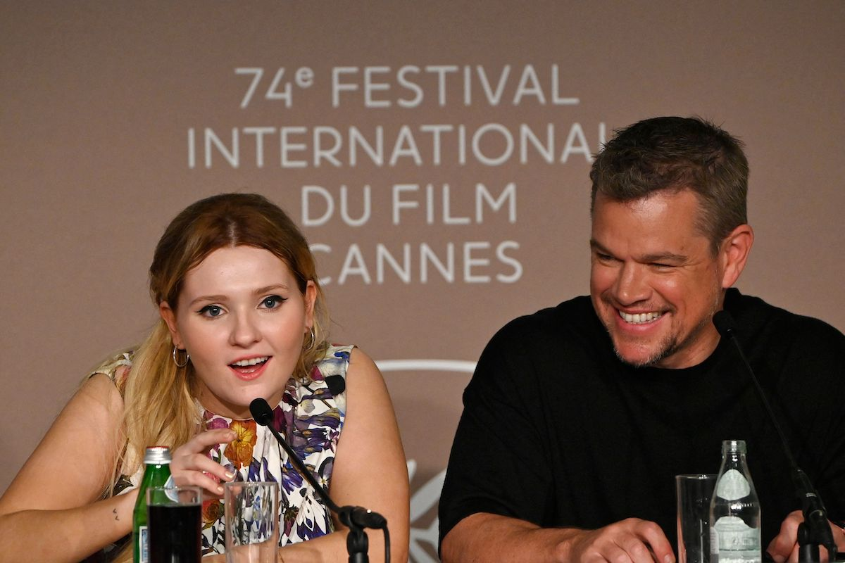 Abigail Breslin speaks into a mic while Matt Damon smiles during a 'Stillwater' press conference at the 2021 Cannes Film Festival