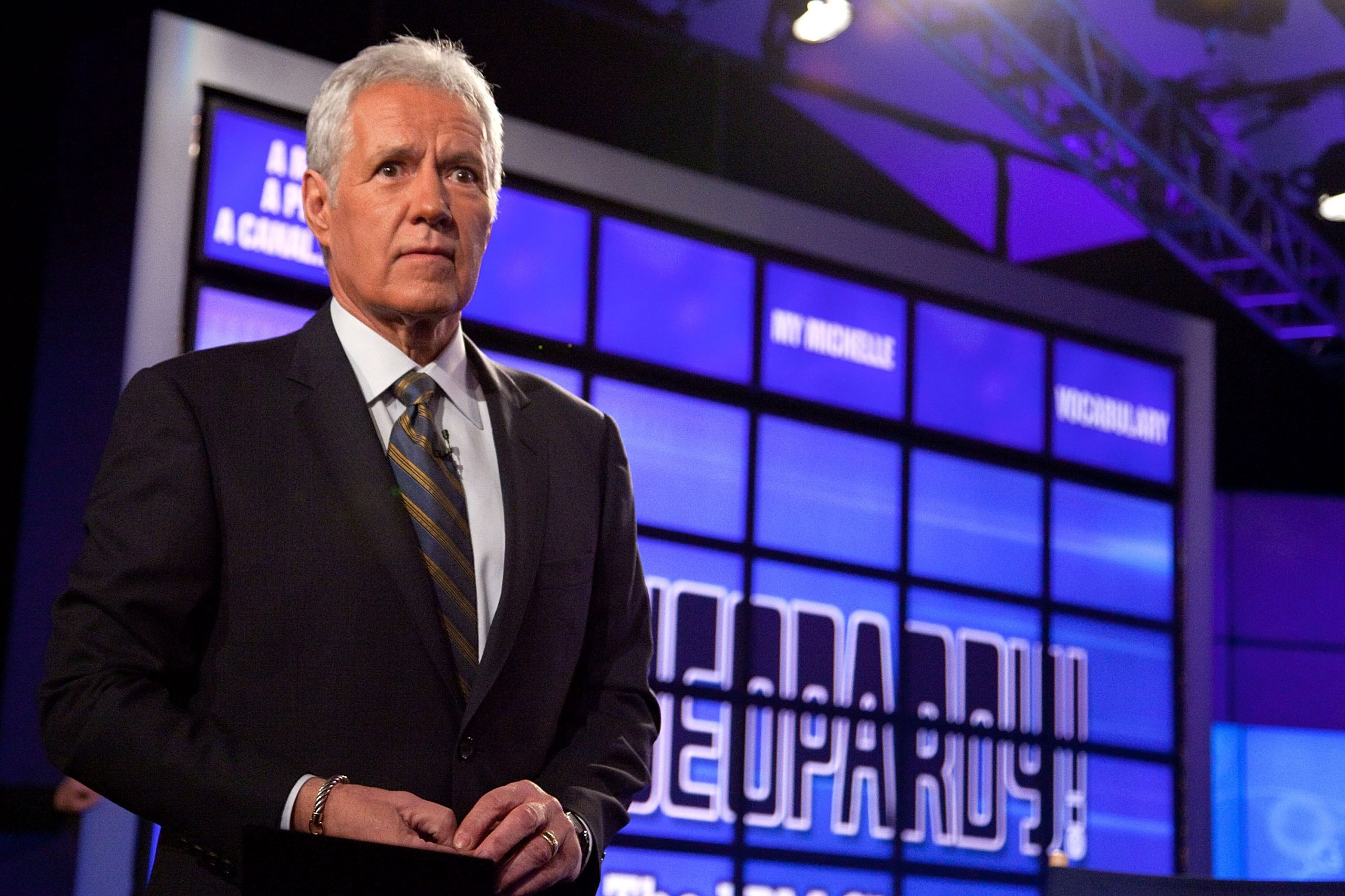 Late 'Jeopardy!' host Alex Trebek stands in front of the iconic game board.
