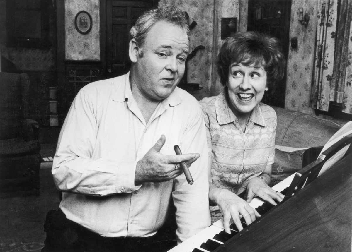 Actors Carroll O'Connor and Jean Stapleton pose by a piano as Archie and Edith Bunker in a scene from 'All in the Family'