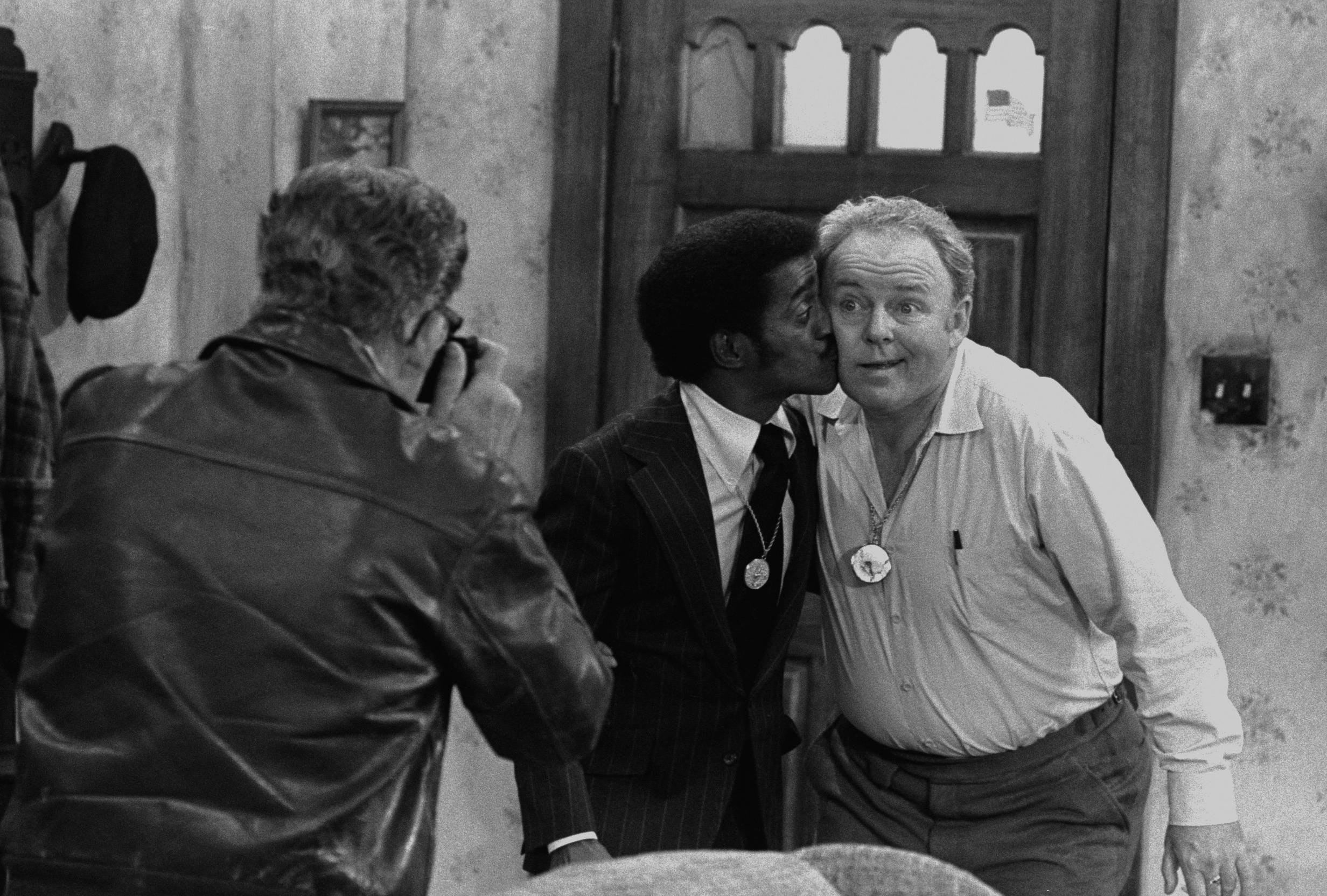 Actor Billy Halop (with camera), entertainer Sammy Davis Jr., and actor Carroll O'Connor in a scene from 'All in the Family'