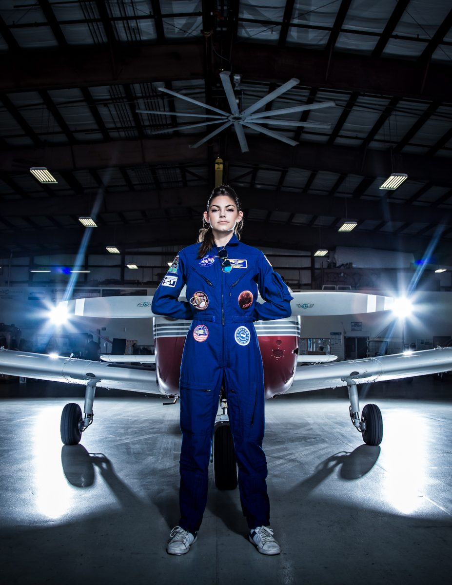 Astronaut Alyssa Carson wearing a blue flight suit and standing in front of a plane