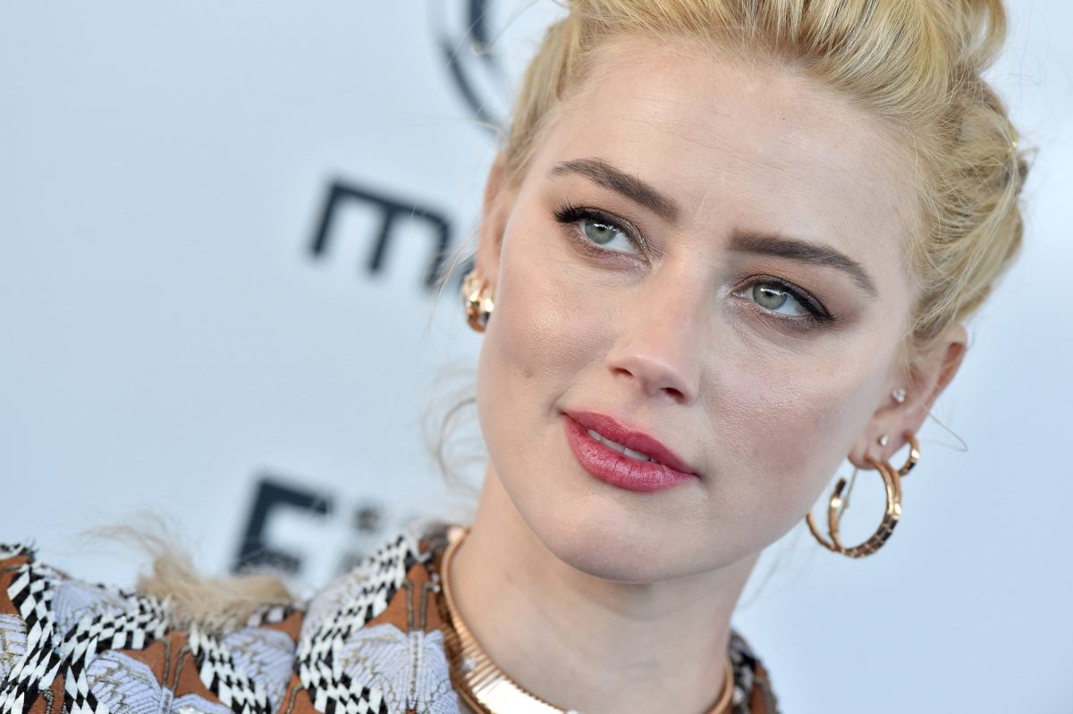 Aquaman 2 star Amber Heard looking to the side with her blonde hair pulled back and gold earrings on