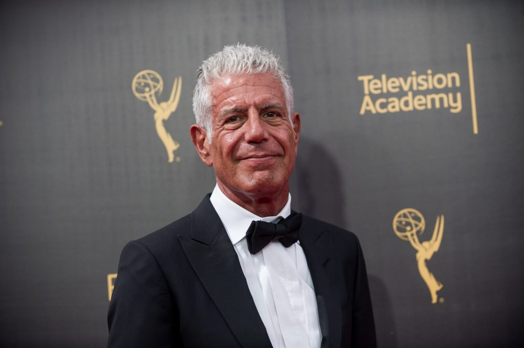 Anthony Bourdain smiling in front of a black background