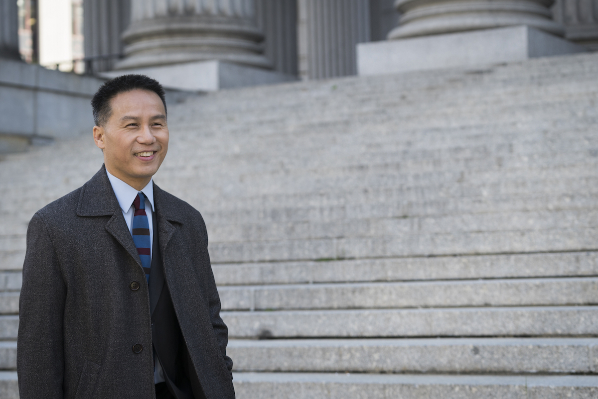Actor BD as Dr. George Huang in 'Law & Order: SVU' smiles as he stands in front of stairs.