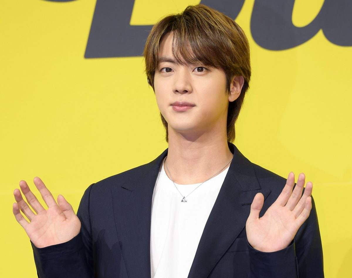 Jin of BTS holds up both hands while stanidng in front of a yellow background at BTS' 'Butter' press conference