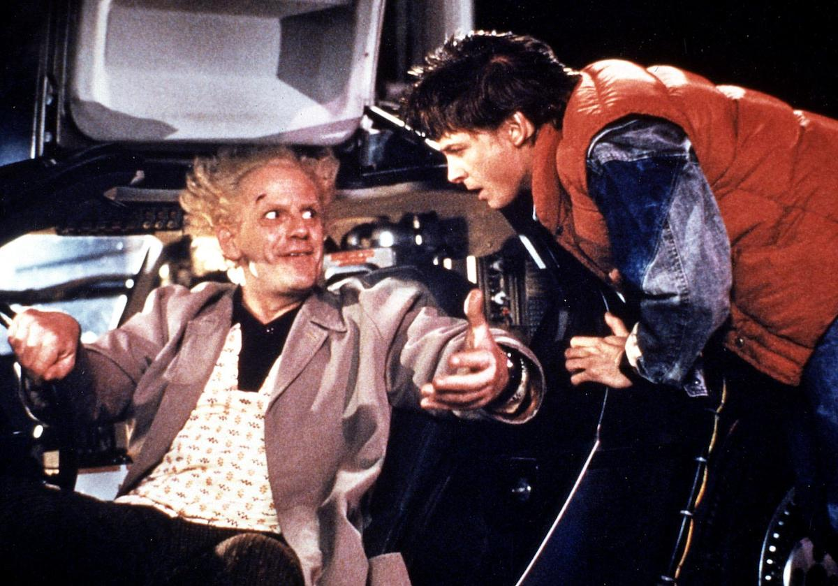 Doc Brown (Christopher Lloyd) sits in the Delorean smiling up at Mary McFly (Michael J. Fox) in 'Back to the Future'