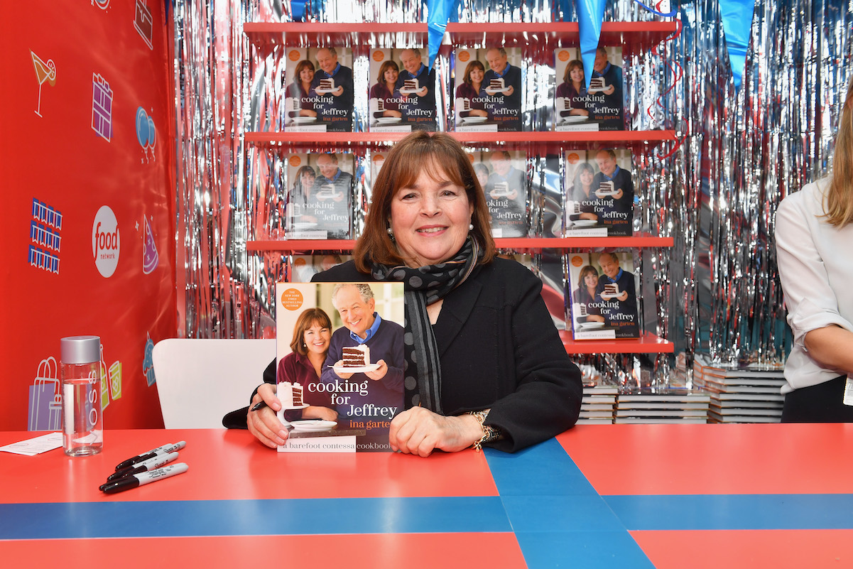 Ina Garten holding her 'Cooking for Jeffrey' cookbook and smiling at an event in 2018