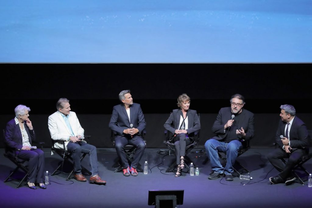 Six people that are from the cast of Disney's 'Beauty and the Beast' sitting in front a black background dressed professionally.