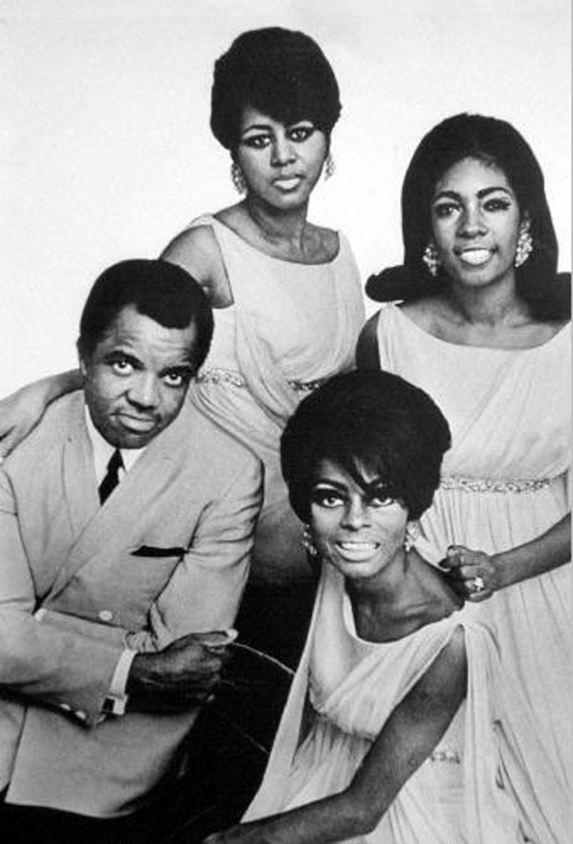 Berry Gordy with Diana Ross and The Supremes smiling for the camera in a black and white photo.