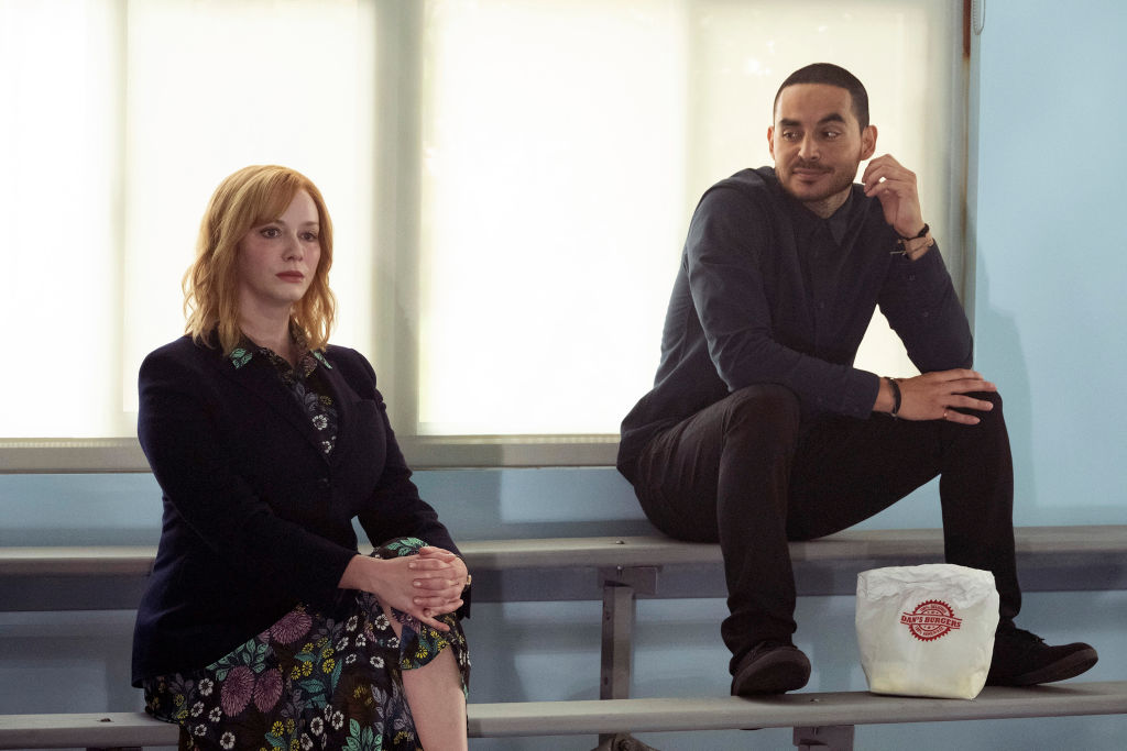 Christina Hendricks as Beth Boland and Manny Montana as Rio sit on the bleachers together. Rio looks over at Beth slyly.