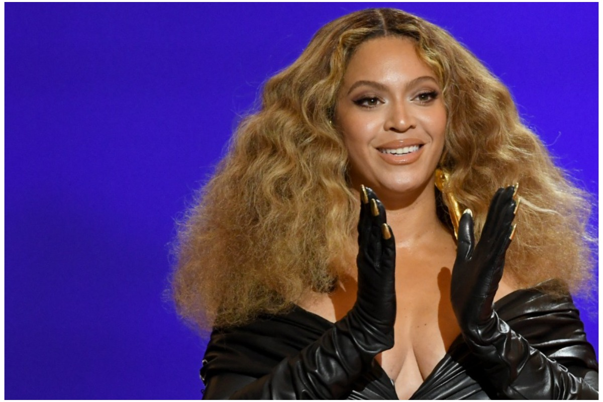 Beyoncé smiling and clapping while attending the 2021 Grammy Awards.