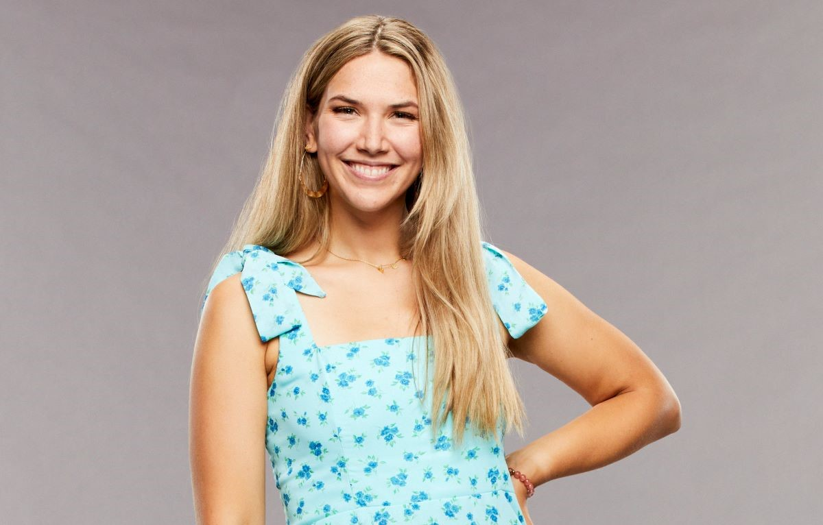Claire Rehfuss of 'Big Brother 23' poses in a blue dress with her hand on her hip smiling.