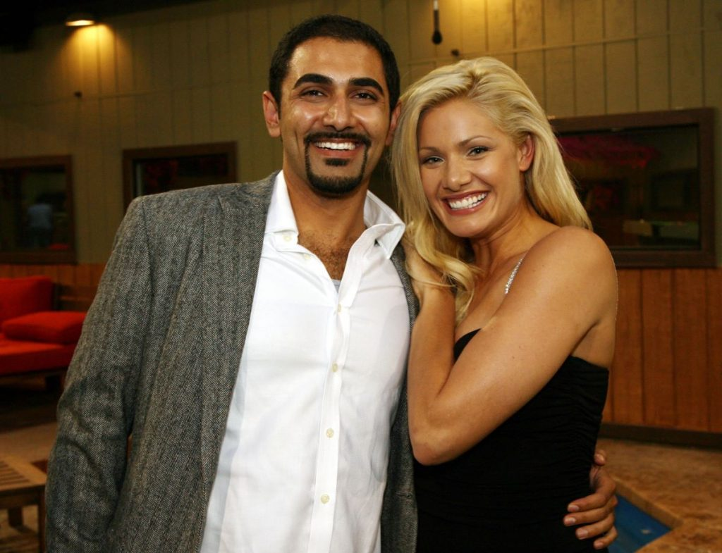 Kaysar Ridha wears a shirt and jacket and Janelle Pierzina wears a black dress as they pose together smiling of 'Big Brother'