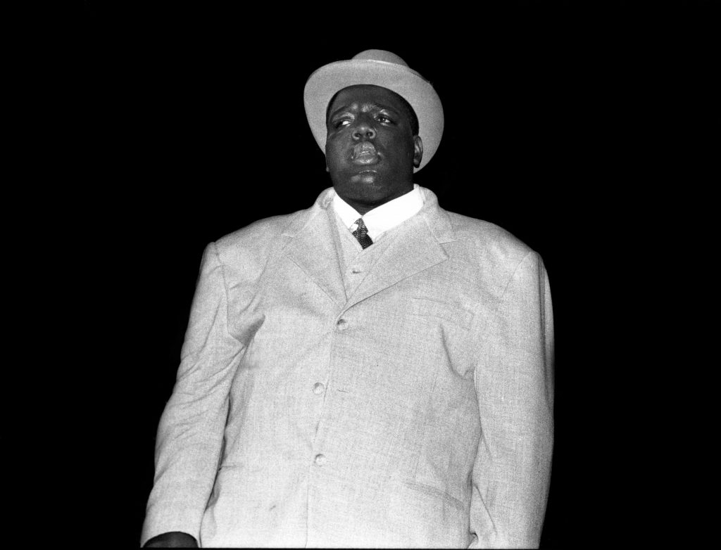 The Notorious B.I.G. wearing a suit and hat