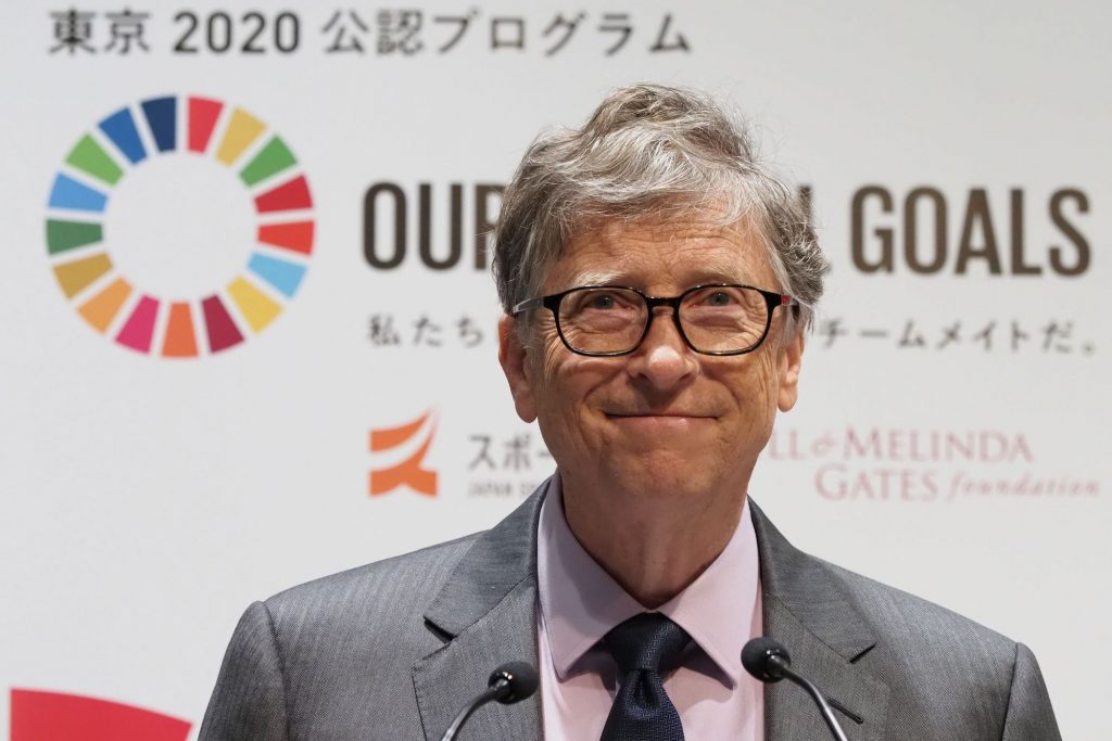 Bill Gates in front of a white and multi color background
