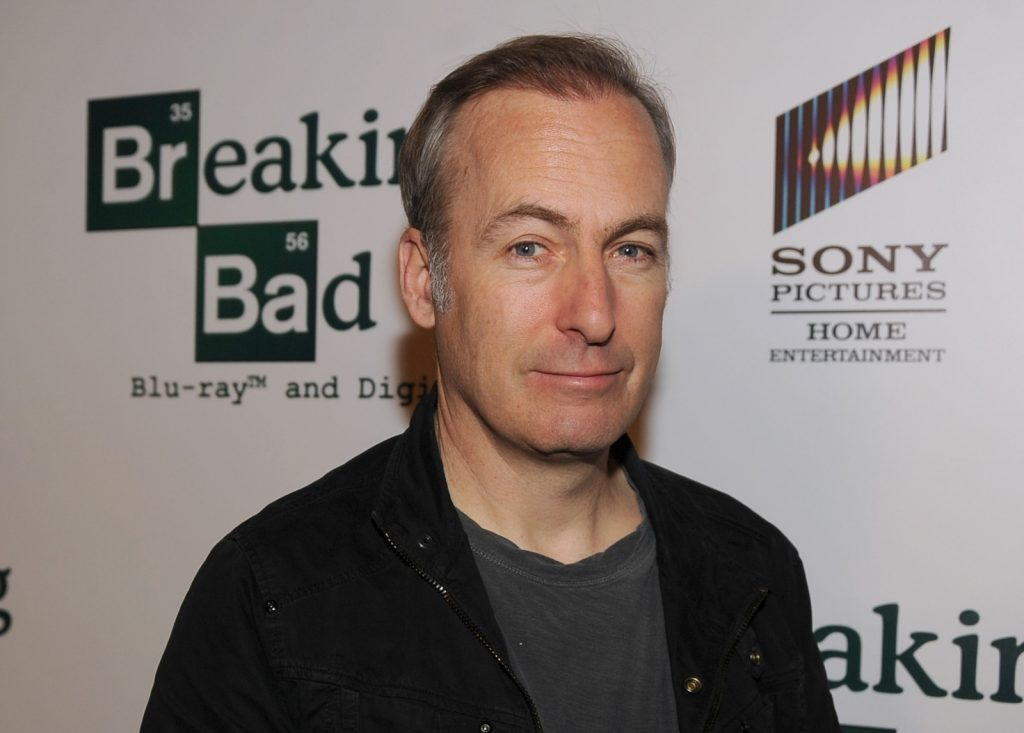 'Better Call Saul' star Bob Odenkirk stands in front of a 'Breaking Bad' and AMC wall wearing a grey shirt and black jacket