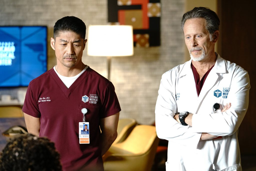 Brian Tee and Steven Weber stand next to each other in an office on the set of 'Chicago Med'