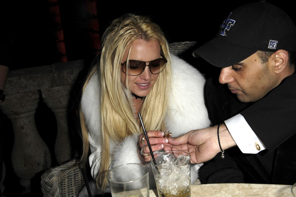 Britney Spears looking at something small in Sam Lutfi's hand