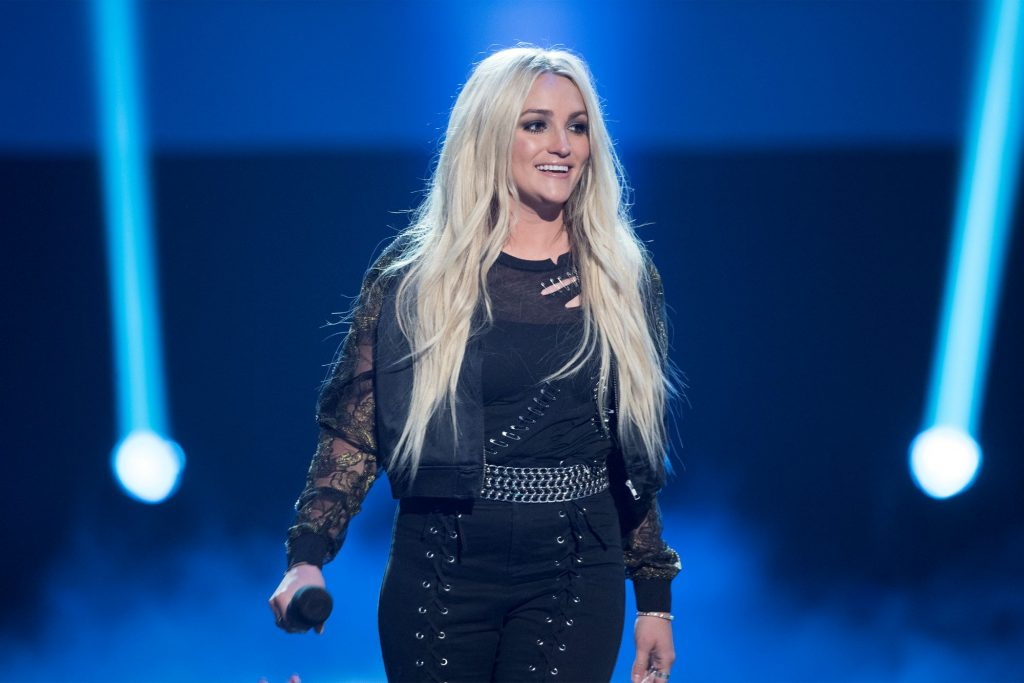 Jamie Lynn Spears stands on a foggy stage with a blue glow and two spotlights shining up on both sides in a black jumper and black jacket with lace sleeves.