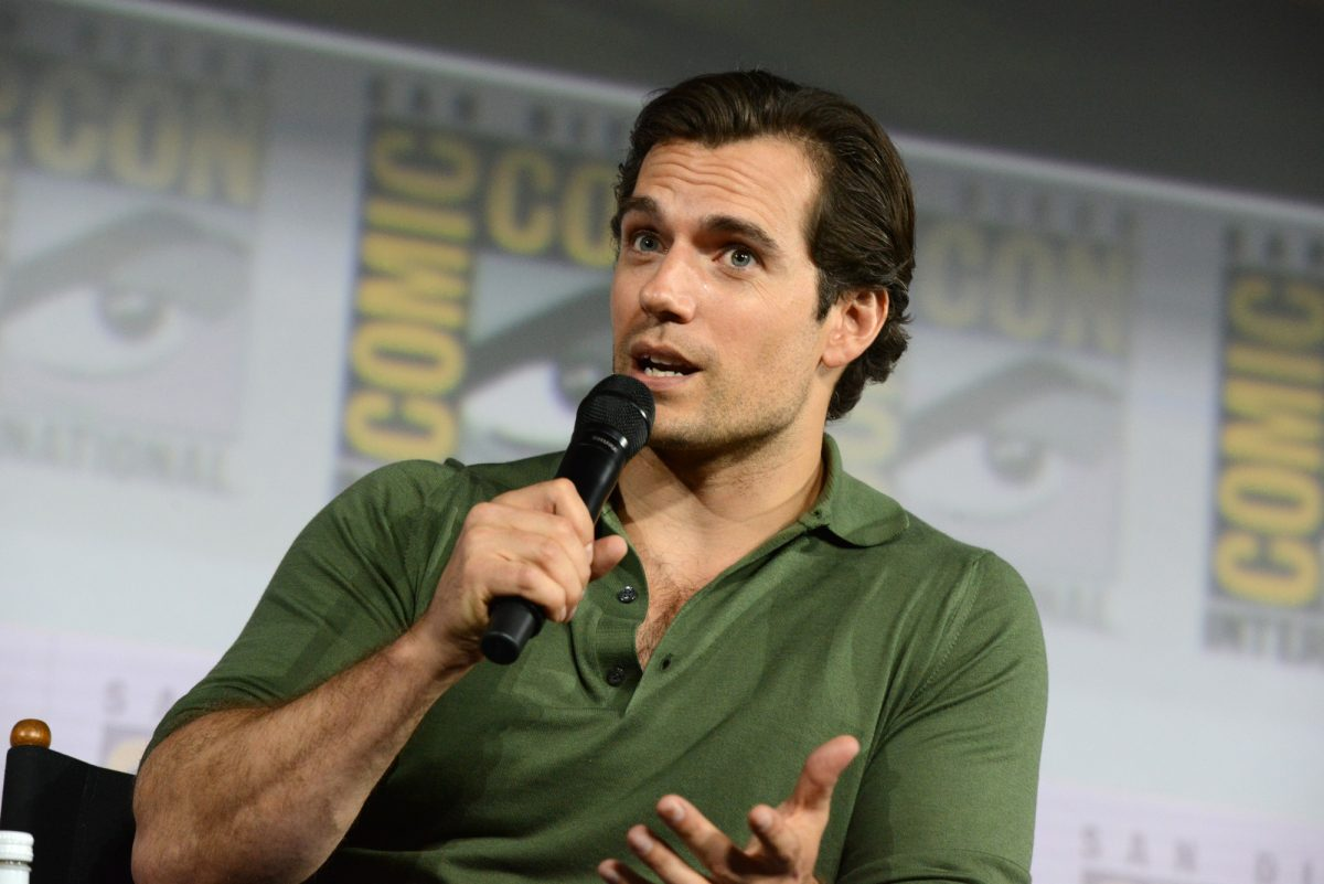 Superman star Henry Cavill wears a green collared shirt and speaks into a microphone at San Diego Comic-Con