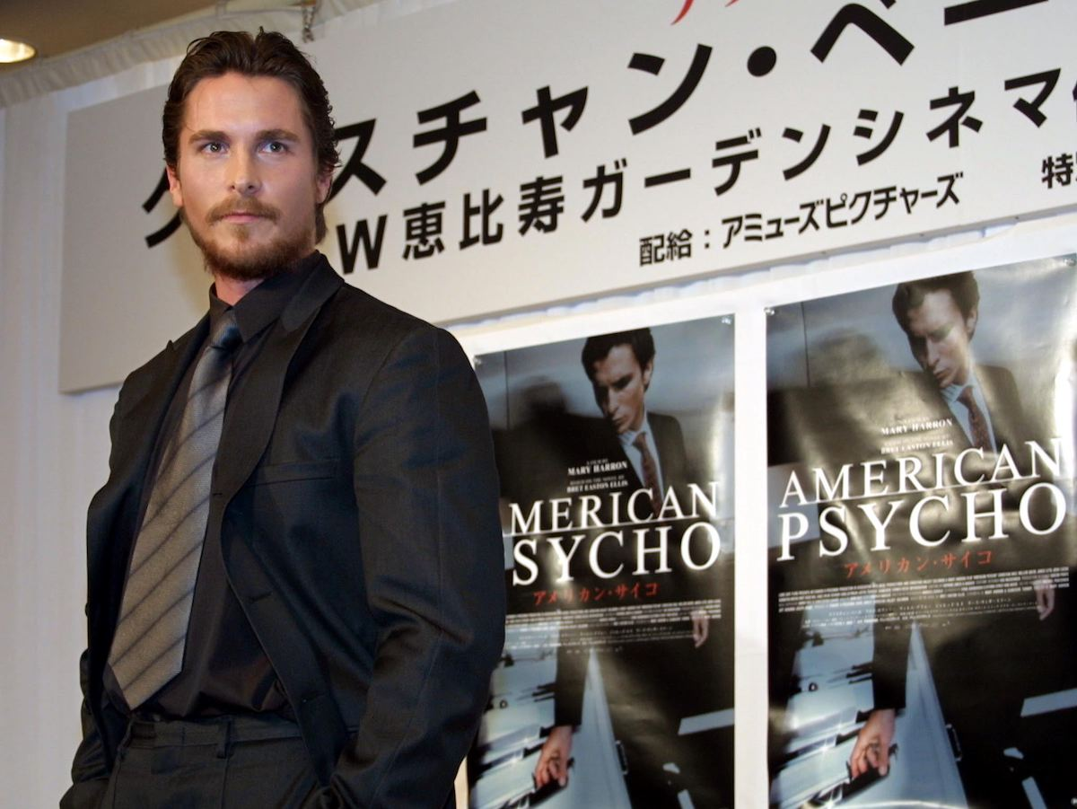 Christian Bale wears a suit and poses in front of 'American Psycho' posters