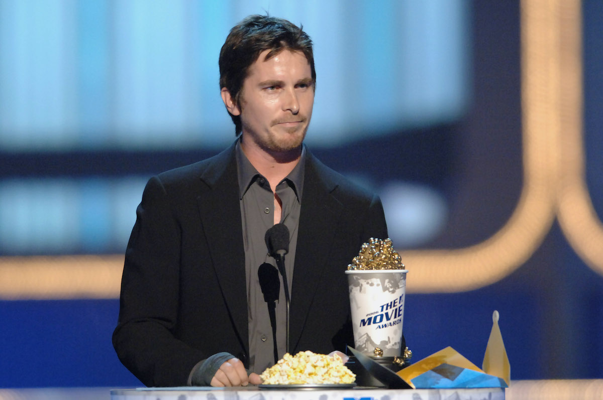 Christian Bale stands at a podium dressed in a jacket