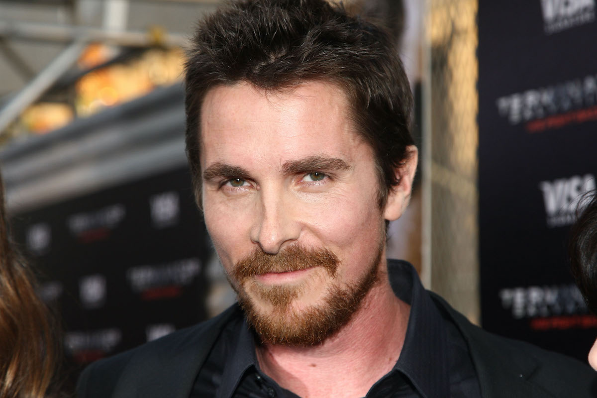 Christian Bale wears a suit and smiles