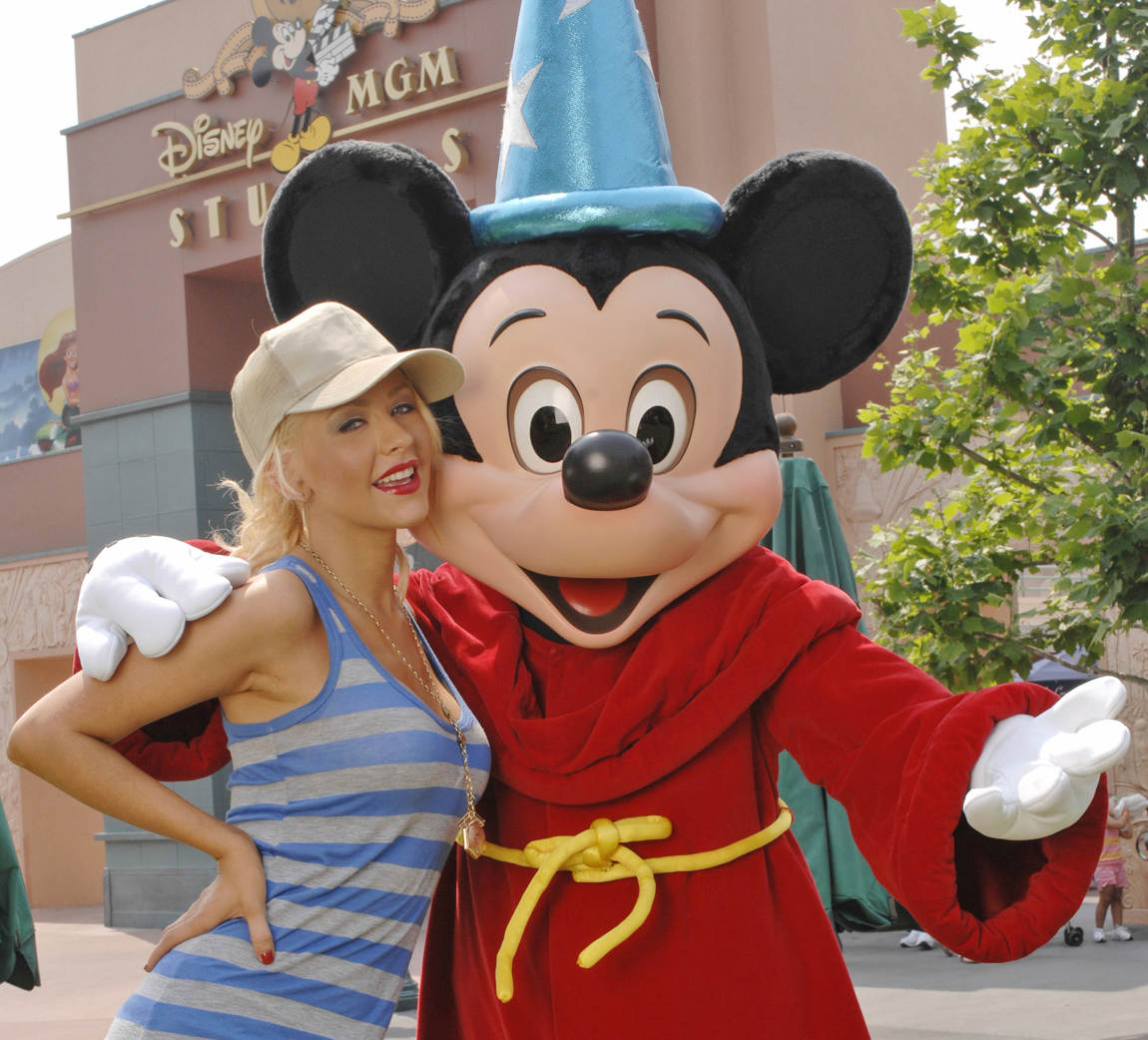 Christina Aguilera poses with Mickey Mouse at the Disney MGM Studios