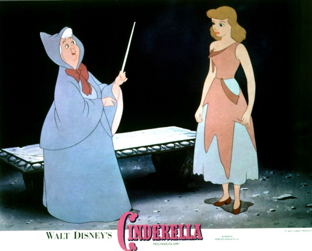 The animated Cinderella in her rags and the fairy godmother in her blue dress with her wand stand in front of a black background with a stone bench behind them.