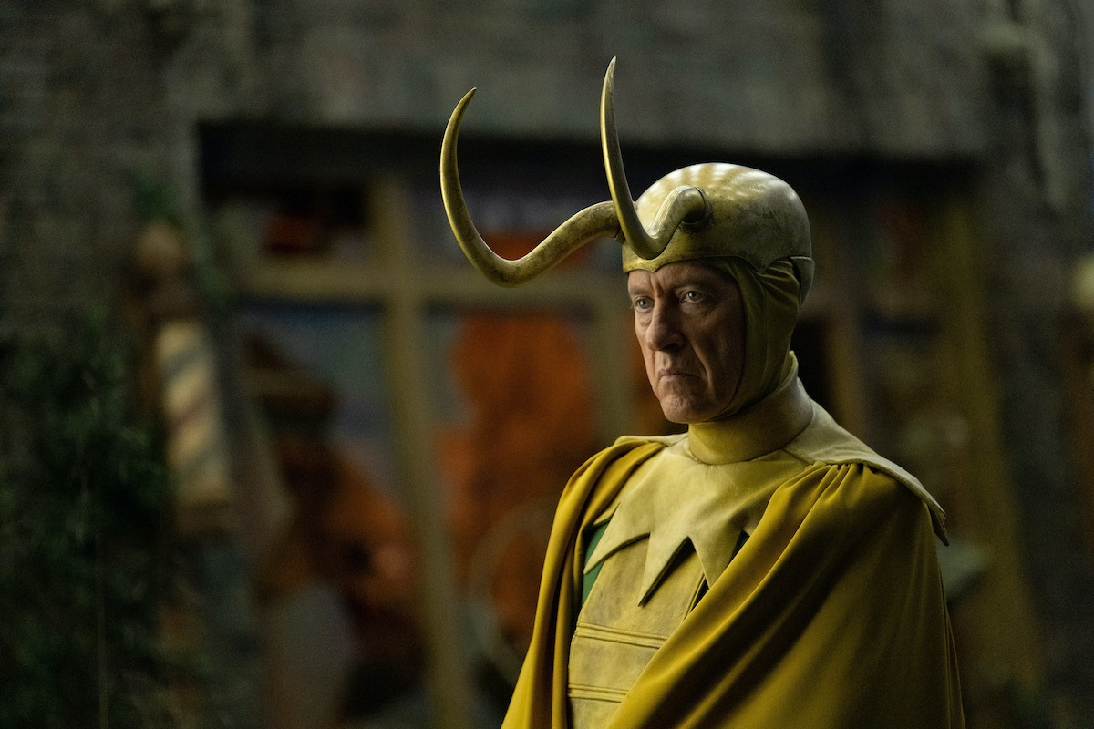 Richard E. Grant as Classic Loki in 'Loki' Episode 5. He wears a gold Loki helmet with long horns, a yellow cape and collar, and green suit.