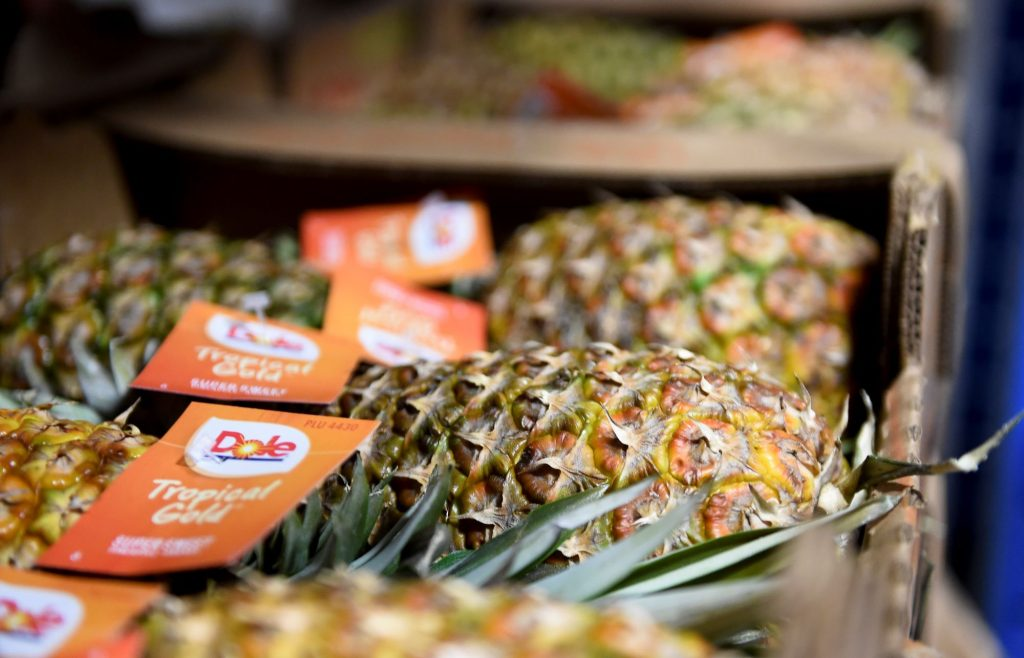 Crates of Dole Tropical Gold pineapples in a grocery store