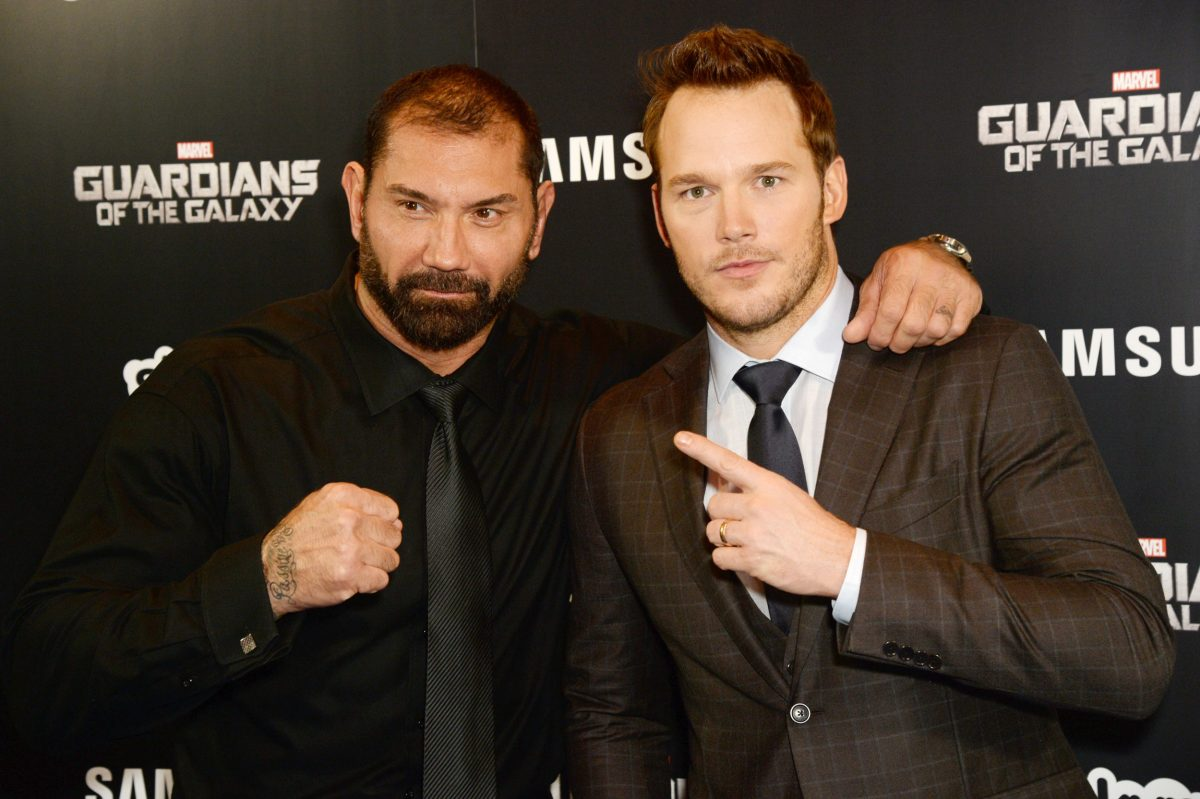 Dave Bautista and Chris Pratt stand in front of 'Guardians of the Galaxy' wall
