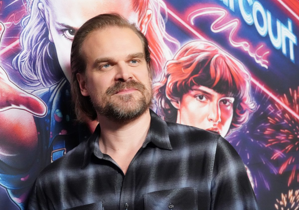 Stranger Things star David Harbour wearing a black and white flannel shirt and standing in front of a Stranger Things wall