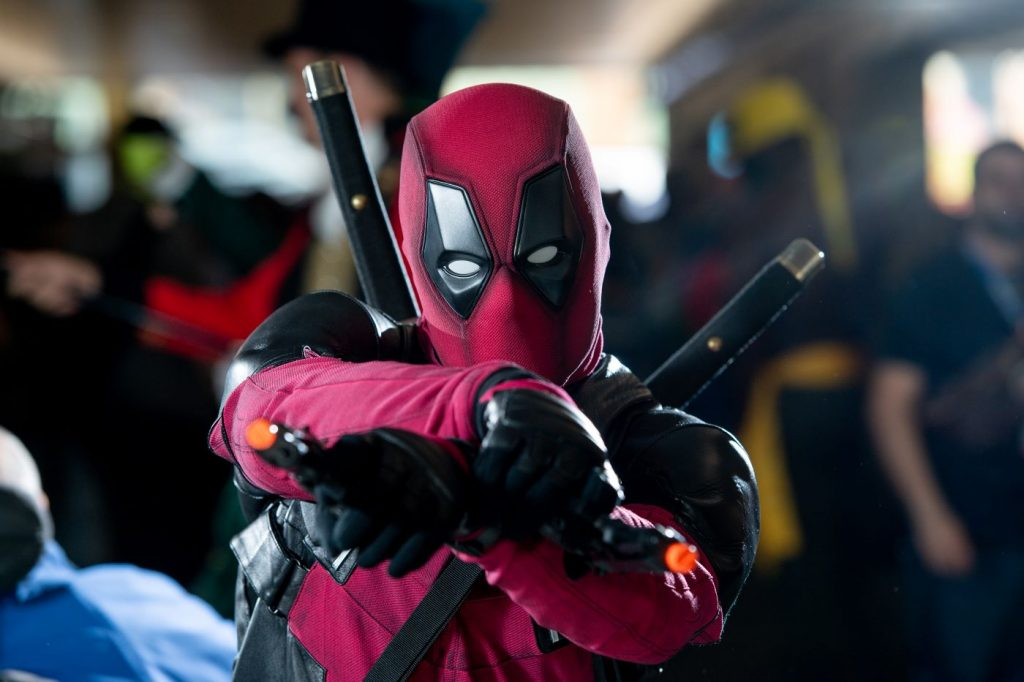 Deadpool character with hands crossed and outreached with a background of people walking blurred.