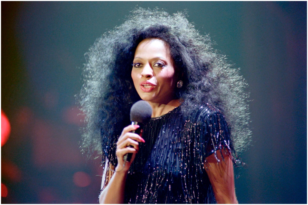 Diana Ross holding a microphone and talking while wearing a black top.