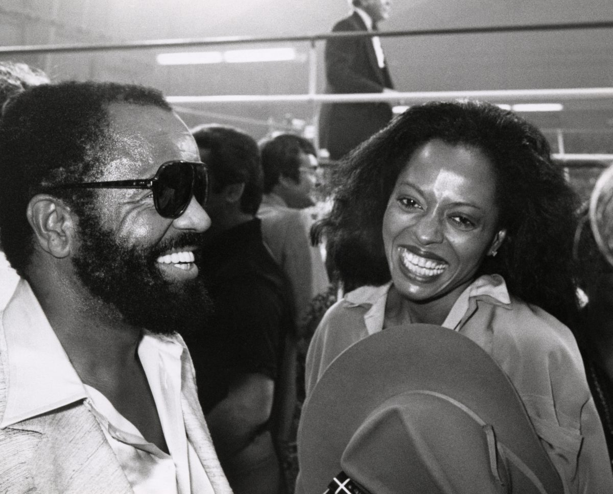 A black and white photo of Diana Ross and Berry Gordy smiling at a boxing match.