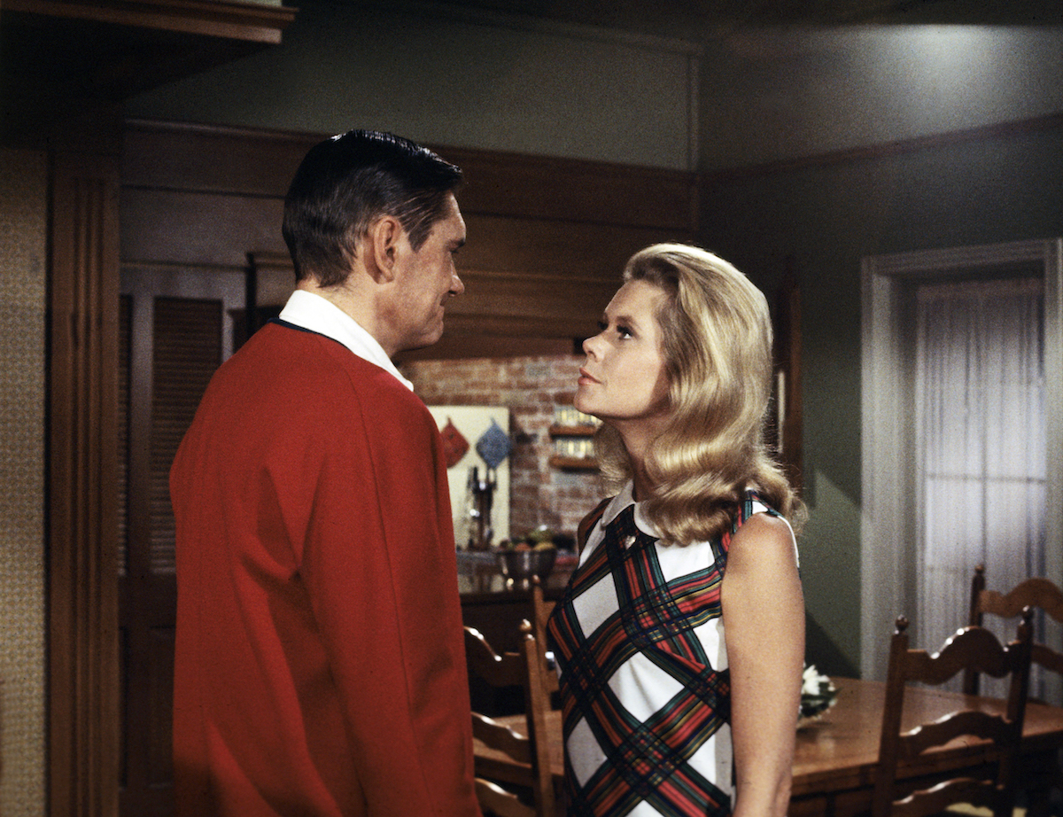 Dick York, in a red sweater, looking at Elizabeth Montgomer, in a plaid dress, in 'Bewitched'